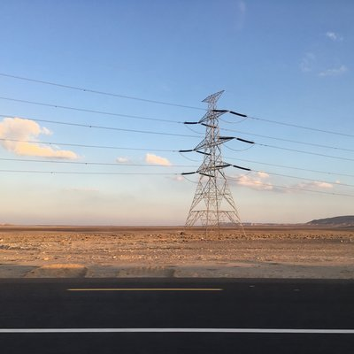 Das Foto zeigt einen Strommast und Leitungen vor blauem Himmel in einer Wüstenlandschaft. Im Vordergrund ist eine Straße zu sehen.