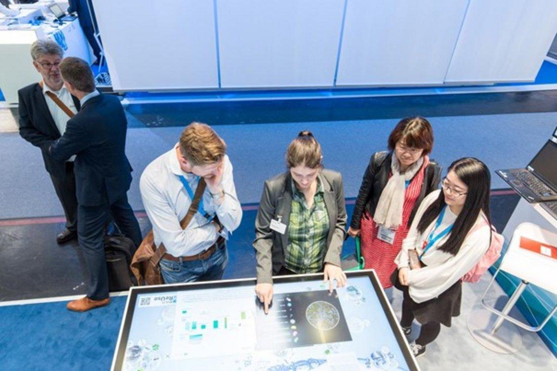 Am Touchtable wird mehreren Messebesuchern die Projektidee interaktiv erklärt.