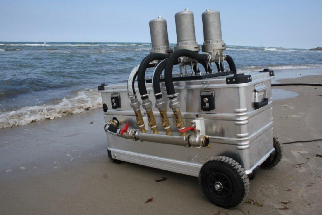 Seitenansicht der 'Rocket'. In einer Aluminium Box befindet sich die Pumpe, um Wasser über die Filter anzusaugen. Die vier Kerzenfilter befinden sich jeweils in einem Edelstahl Gehäuse und sind senkrecht auf der Box angebracht. Sie sind über Schläuche mit der Pumpe und dem Einlassschlauch verbunden.