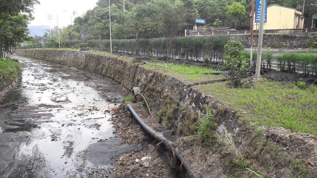 Blick in ein beidseitig durch Mauern begrenztes Flussbett, das mit dunkelgrau gefärbten, groben und feinen Sanden bedeckt ist und in dem sehr wenig Wasser fließt