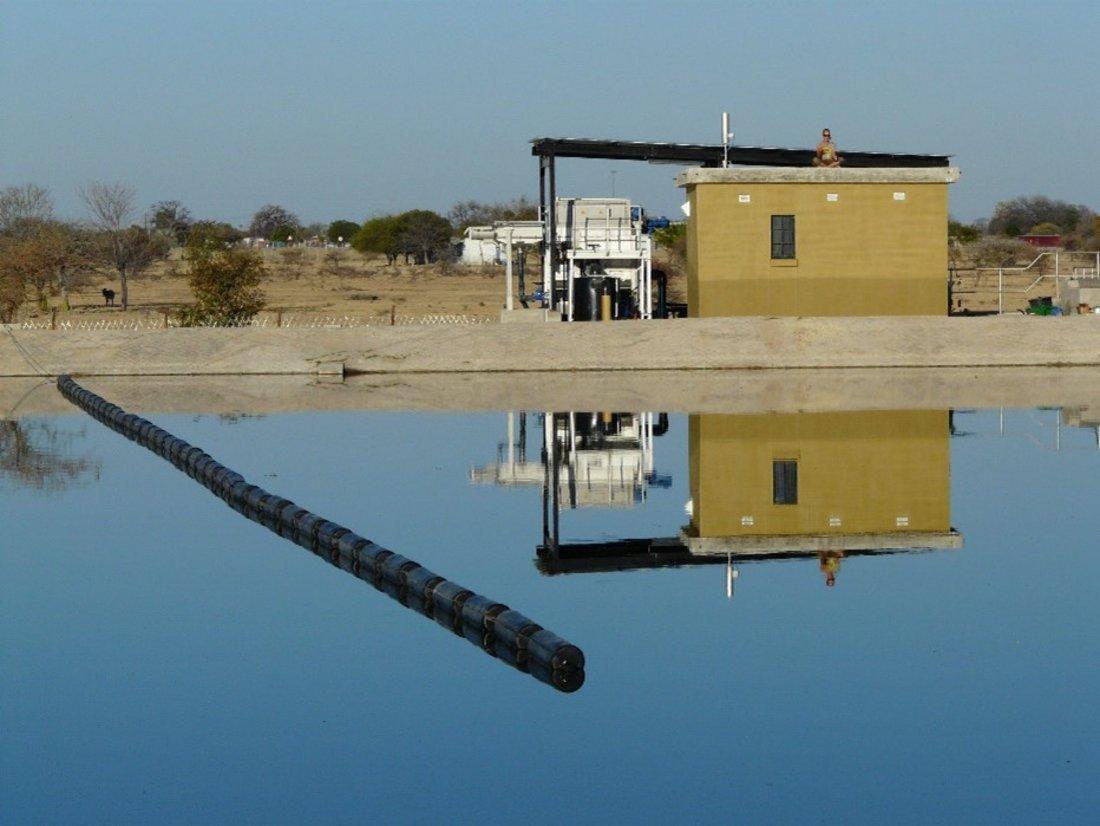Im Vordergrund Wasseroberfläche des ersten Abwasserteiches mit installierter schwimmender Leitwand. Im Hintergrund Vorbehandlung mit Mikrosieb und Schaltwarte.