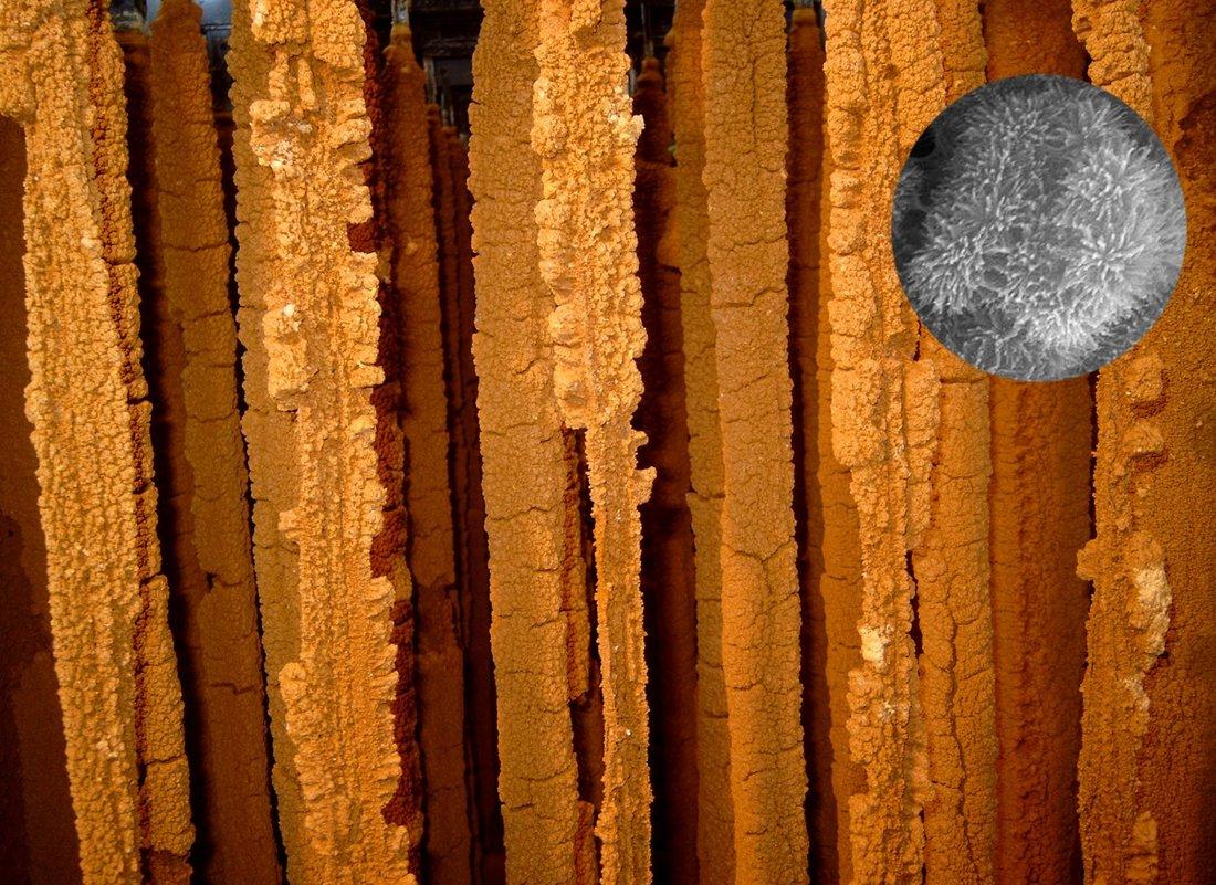 Blick in einen Bioreaktor, in dem eisenoxidierende Bakterien die Bildung von Schwertmannit bewirken. Schwertmannit ist ein Eisen-oxid-hydroxid-sulfat Mineral. Der runde Bildausschnitt zeigt in einer Rasterelektronenmikroskop-Aufnahme eine extreme Vergrößerung des Minerals