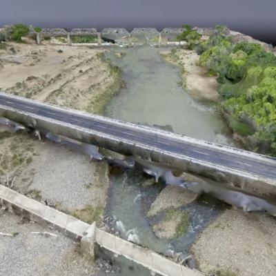 Es ist ein 3D-Modell eines Flusses und seiner angrenzenden Gebiete zu sehen. Über den Fluss führt eine Straße.