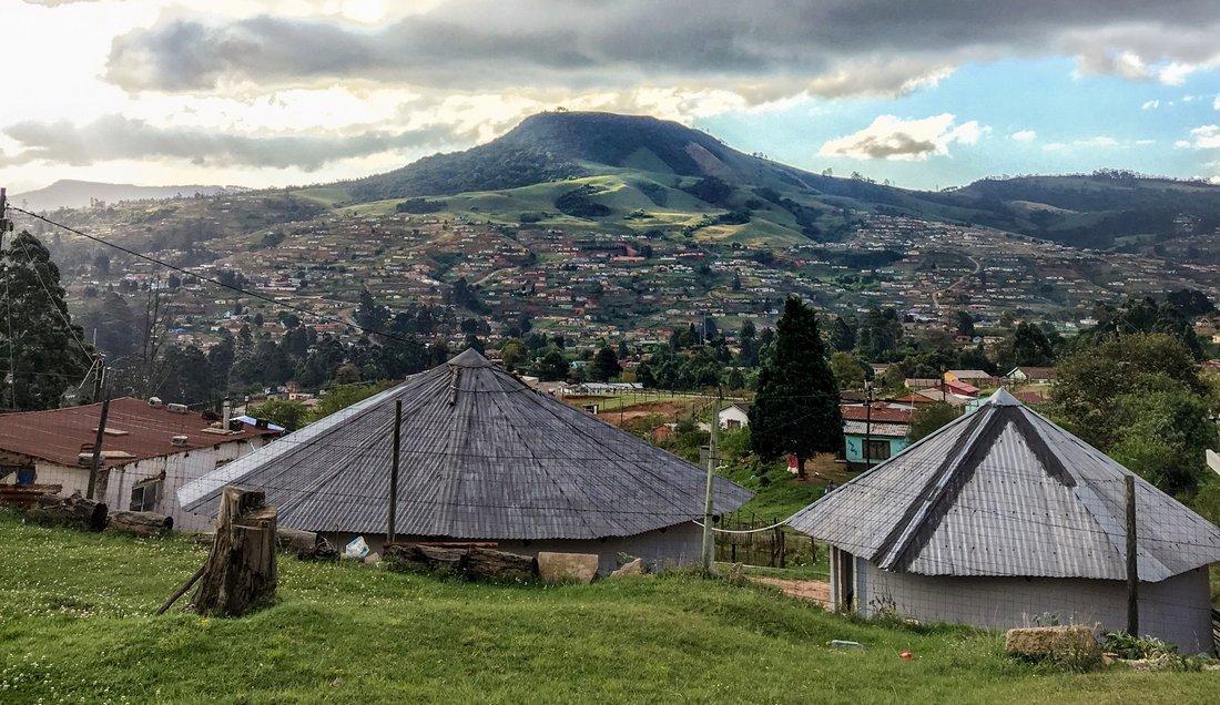 Das Bild zeigt eine hügelige Landschaft. Eine Siedlung bedeckt teilweise die Hänge. Die Hügelkuppen sind teilweise mit Wald bedeckt. Im Vordergrund befinden sich zwei traditionelle Zulu-Hütten (Rundhütten mit Spitzdächern) und eine Wohnhütte..