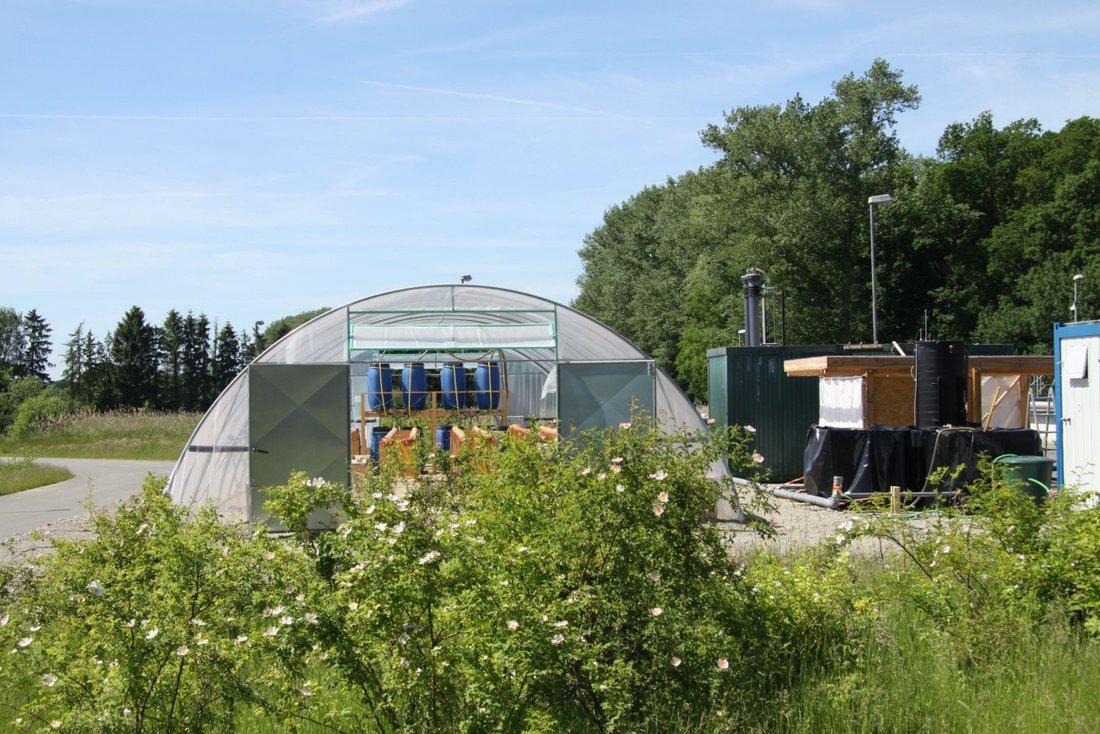 Blick auf das Foliengewächshaus mit den Wassertanks und den Pflanzrohren des hydroponischen Systems sowie daneben auf die Containerteile der Pilotanlage zur Aufbereitung des kommunalen Abwassers