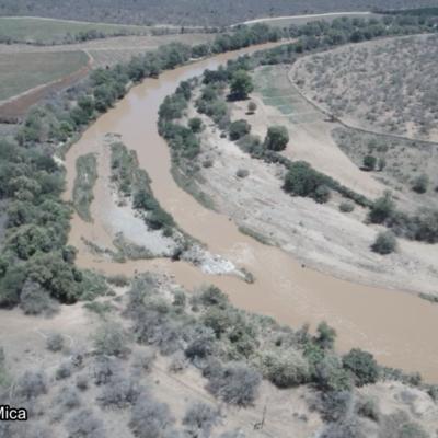 Es ist eine Luftaufnahme eines Flusses und seines Umlandes zu sehen. Über den Fluss führt eine betonierte Brücke. Das Flusswasser ist braun, die Erde des Umlandes besitzt ebenfalls eine braune Färbung und wird von einigen grünen Bäumen und Büschen durchzogen. Unten links im Bild steht: Olifants River bei Mica.