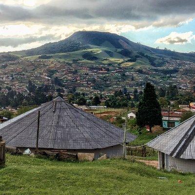 Das Bild zeigt eine hügelige Landschaft. Eine Siedlung bedeckt teilweise die Hänge. Die Hügelkuppen sind teilweise mit Wald bedeckt. Im Vordergrund befinden sich zwei traditionelle Zulu-Hütten (Rundhütten mit Spitzdächern) und eine Wohnhütte.