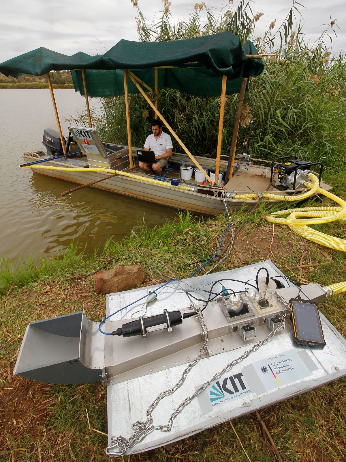 Im Vordergrund ist der Unterwasserströmungskanal zu sehen, welcher mit Kameras, Beleuchtung und Messtechnik ausgestattet ist. Über einen Schlauch ist er mit einer Pumpe auf einem Messboot verbunden